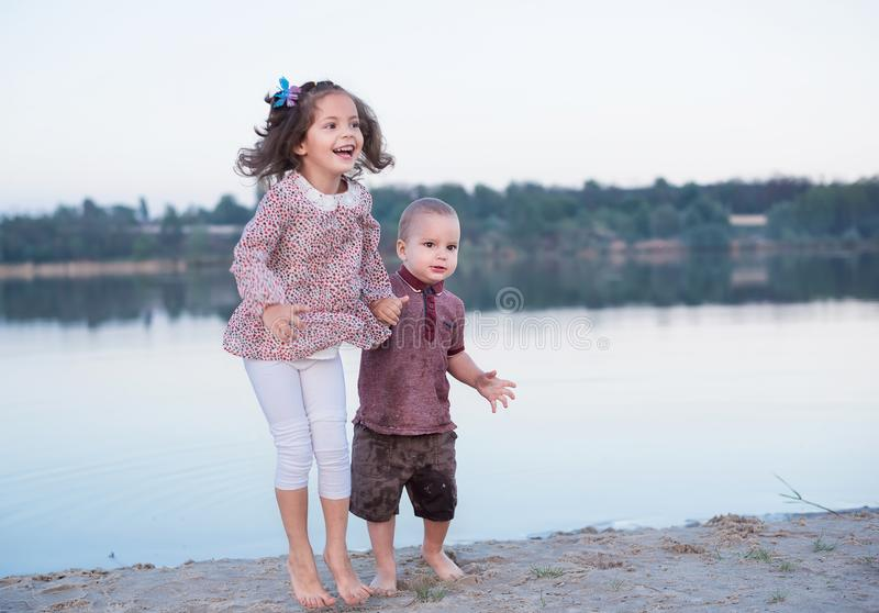 Little brother and the sister have fun near the river. Happy childhood royalty free stock photography