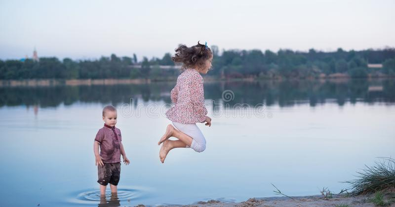 Little brother and the sister have fun near the river. Happy childhood stock photography