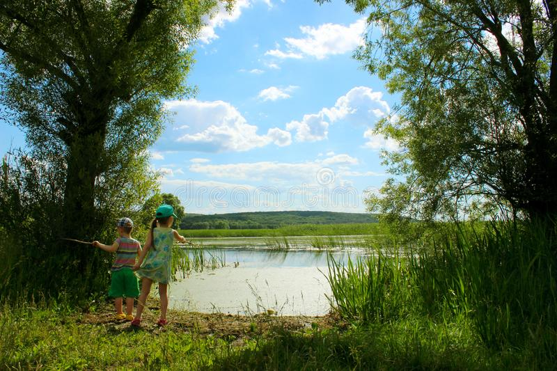 Little brother and sister olaying near the river, back view. People, family, nature concept. royalty free stock images