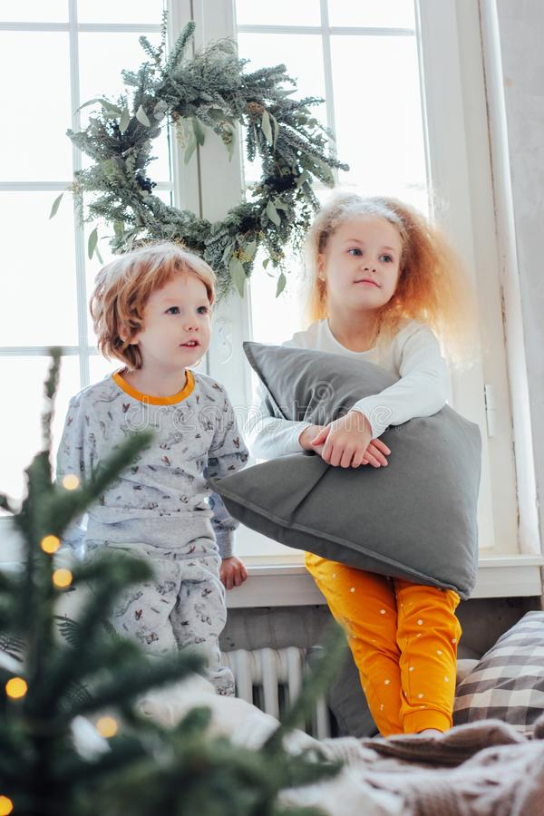 Little brother and sister in pajamas on the bed, Christmas morni royalty free stock photo
