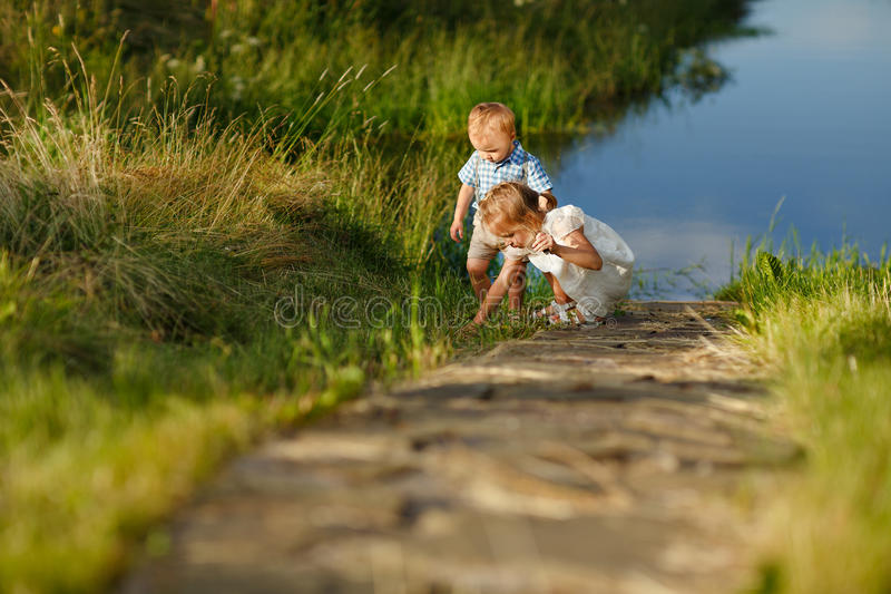 Little brother and sister playing in the grass on a background o. F lake at sunset in summer royalty free stock photography