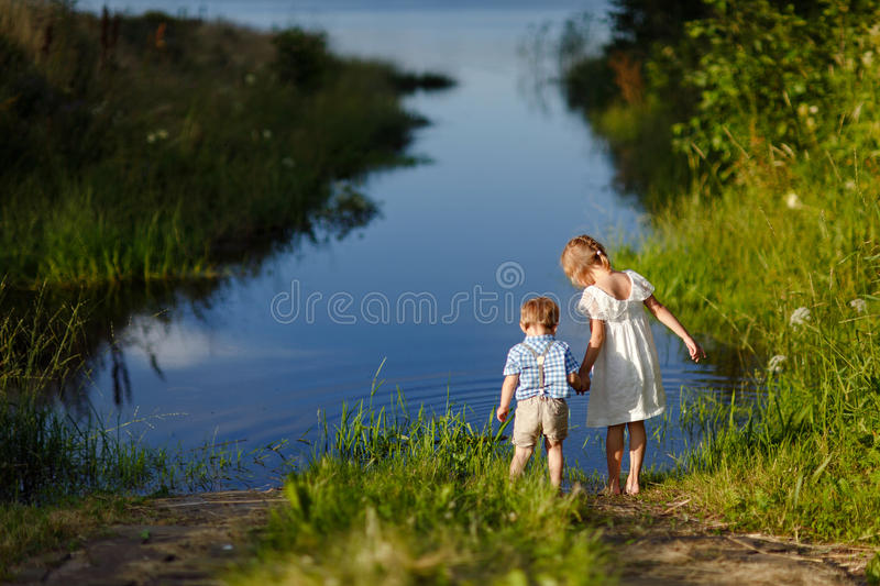 Little brother and sister playing in the grass on a background o. F lake at sunset in summer royalty free stock photos