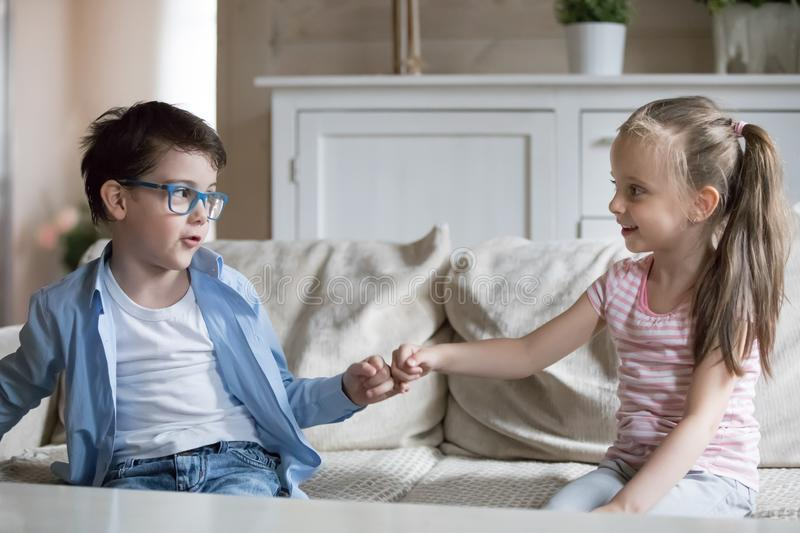 Little brother and sister reconcile after fight joining pinkies. Adorable preschool kids sitting on sofa at home. Little children reconcile after fight or stock photos