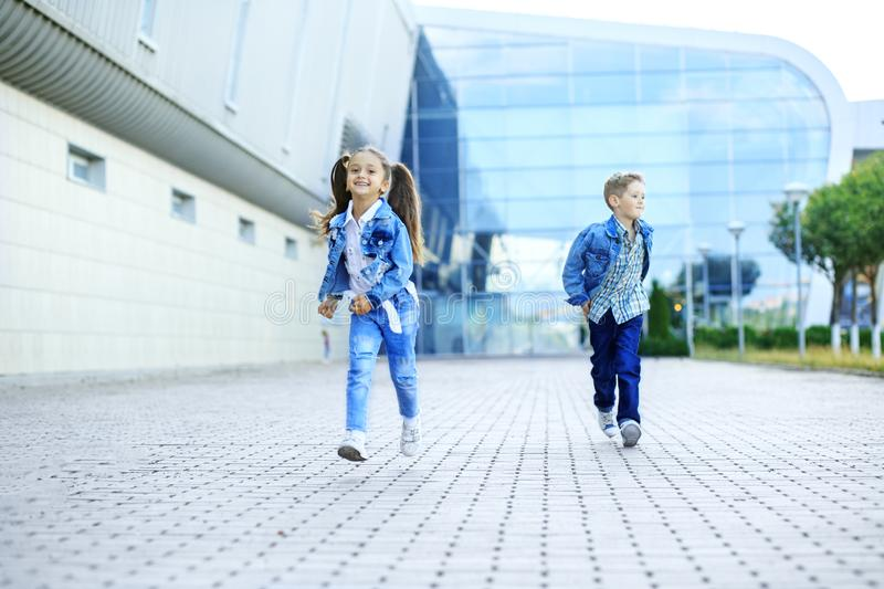 Little brother and sister run down the street. The concept of childhood, family, education. And school royalty free stock photography