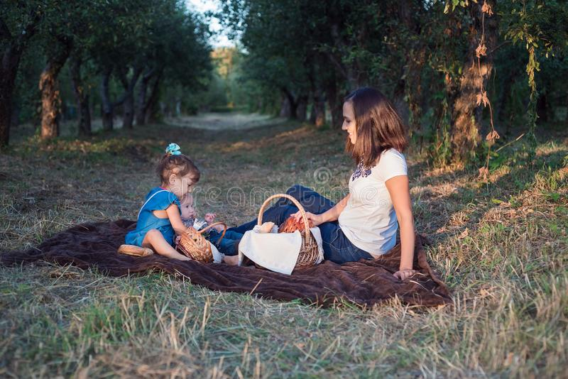 Little brother and sister sit in a row at a family picnic. Time for family stock images