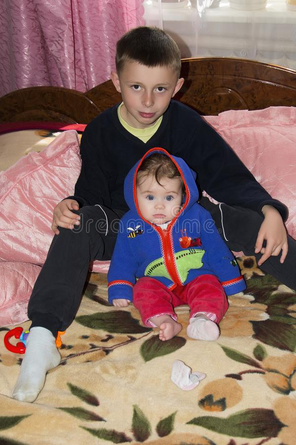Little brother and sister are sitting on the bed in the room stock photo
