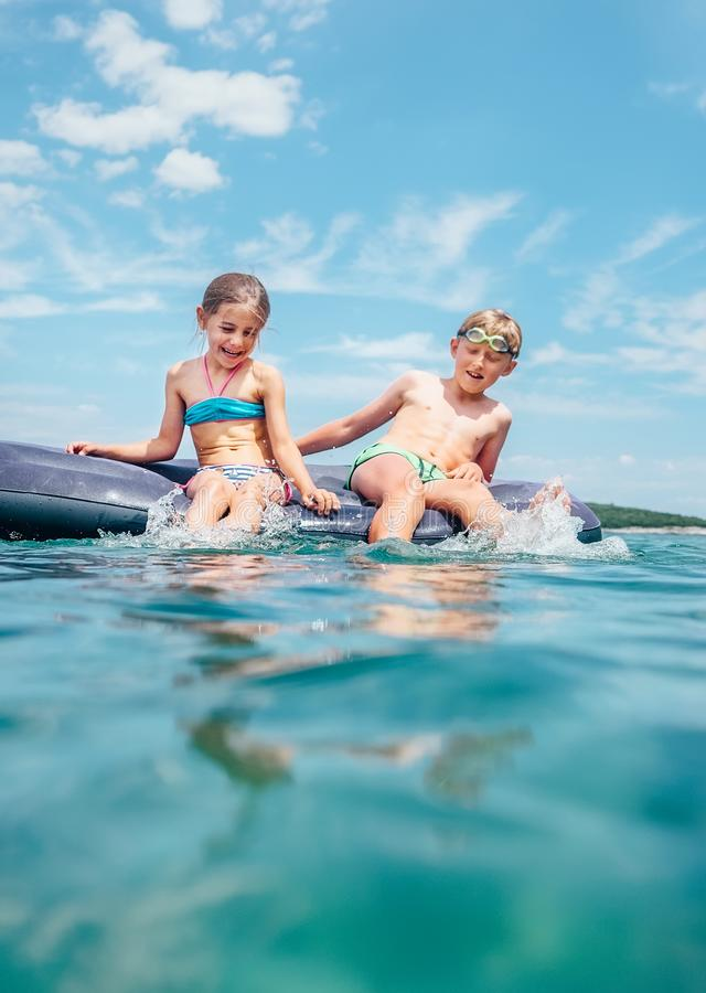 Little brother and sister  sitting  on inflatable mattress in the Adriatic sea. Happy summer holidays concept image royalty free stock images