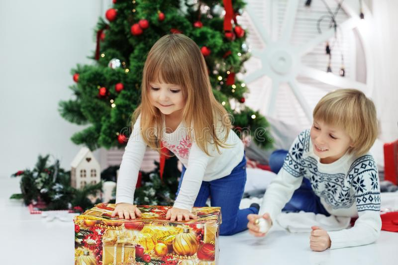 Little brother and sister unpack gifts. The concept of Christmas royalty free stock photos
