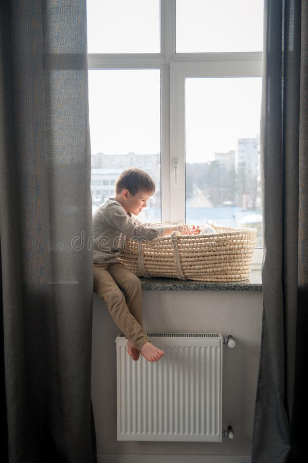 Little brother is sitting near the window with himnewborn sister in the cradle. Children with small age difference royalty free stock photography