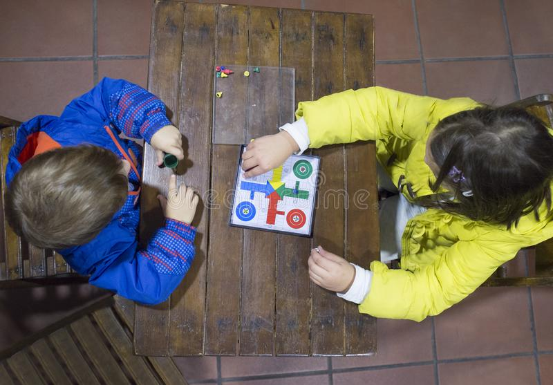 Little brothers playing Parchis over wooden vintage table. Overhead view. Traditional board game royalty free stock photo