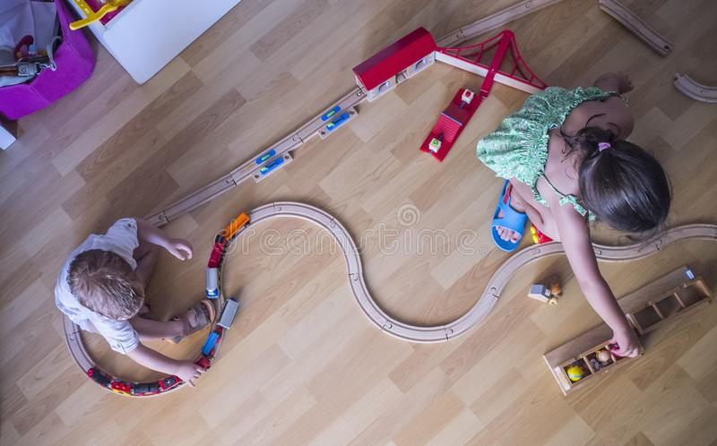 Little brothers playing with wooden toy train. Top view. Educational toys stock photo