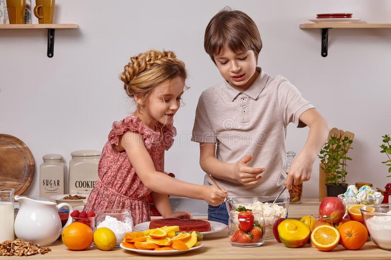 Little friends are making a cake together at a kitchen against a white wall with shelves on it. royalty free stock photos