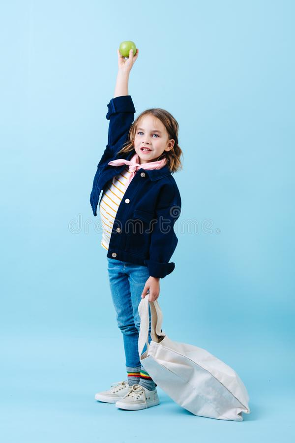 Little girl with an eco bag is holding apple high above her head royalty free stock photos