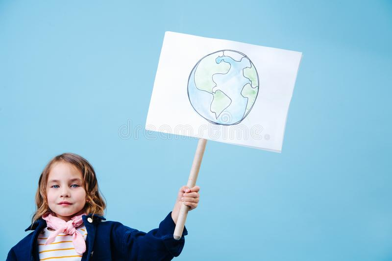 Little girl holding planet earth sign in protest against waste crisis royalty free stock photo