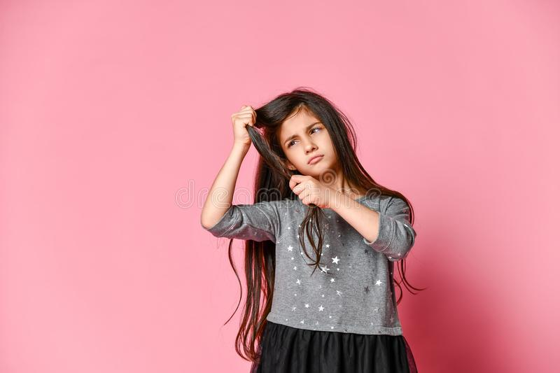 Little brunette girl with long hair holds a strand of her hair and looks at it. Hair care and haircut. stock images