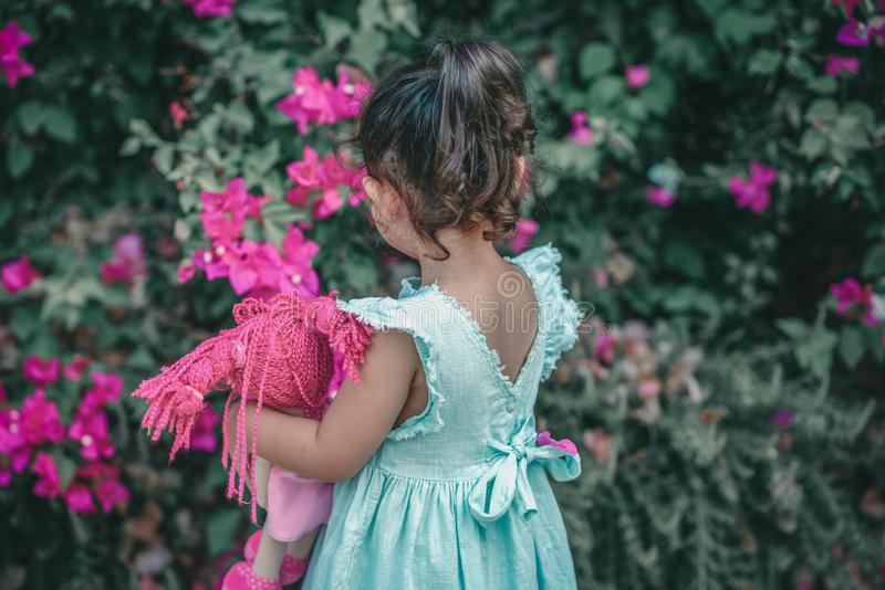 Little brunette girl in a mint color dress in the garden. Cute child holding doll. stock photo