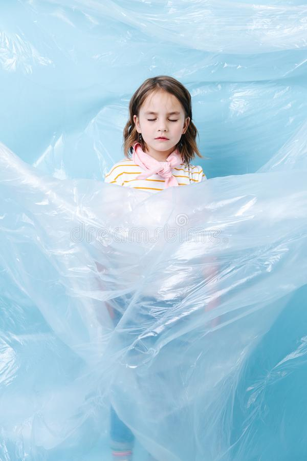 Little girl is wrapped in plastic in protest of waste crisis stock photography