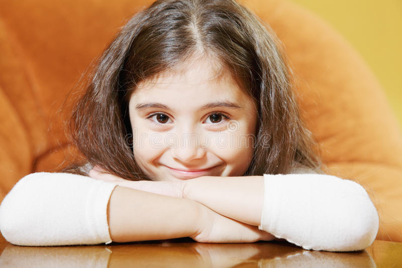 Little brunette sitting at table royalty free stock photos