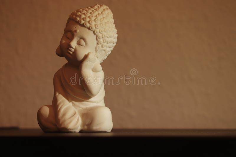 Little buddha sleeping peacefully in a sitting position stock images