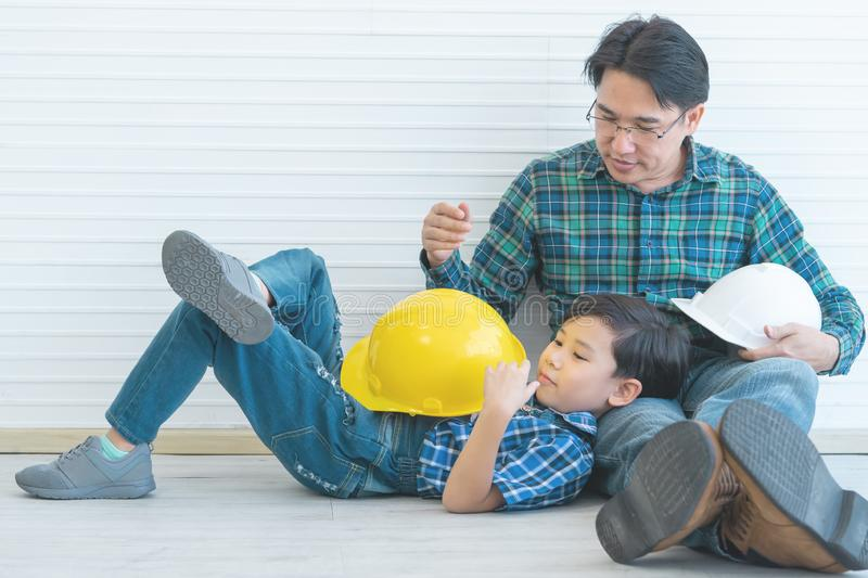 Builder boy is sitting on Father lap for Father day togetherness concept. Little builder boy is sitting on Father lap for Father day togetherness concept royalty free stock photos