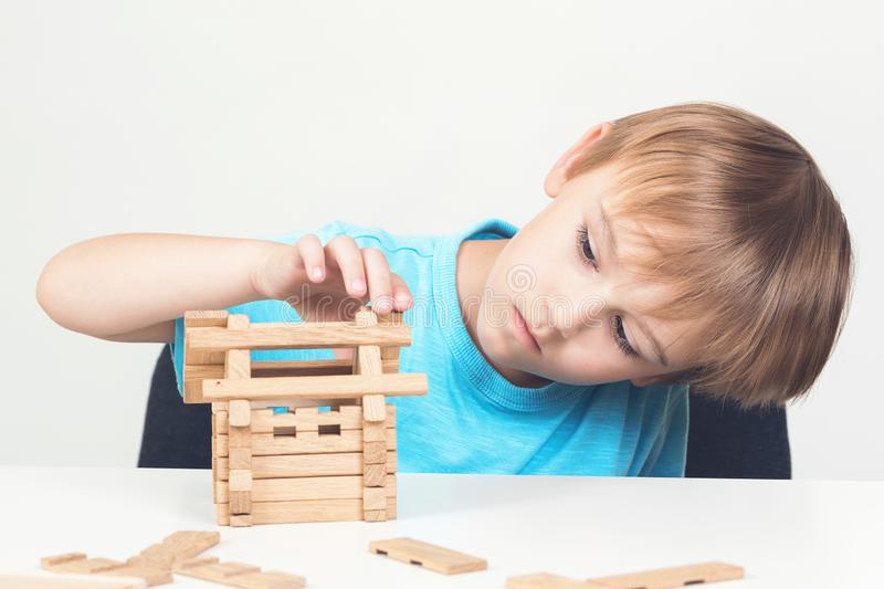 Little builder create house miniature from wooden blocks. Copy space. Childhood. Child dreams about family home. Toy blocks house. Cute little boy playing with royalty free stock photography