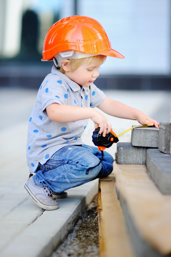 Little builder in hardhats with ruler working outdoors. Portrait of cute little builder in hardhats with ruler working outdoors stock photo