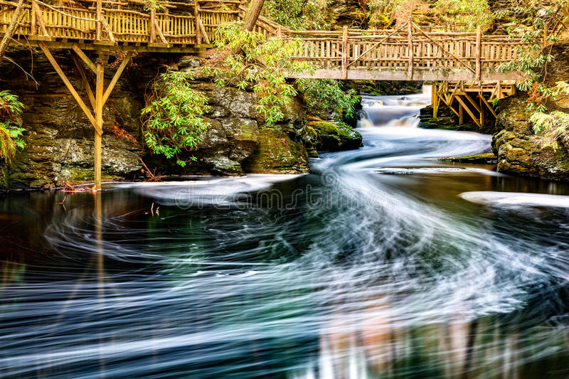 Little Bushkill creek. Meanders through the forest and leaves long exposure foam trails under wooden bridges. Bushkill Creek is a tributary of the Delaware royalty free stock photo
