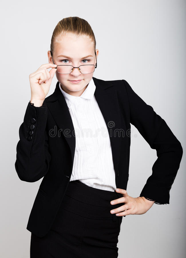 Little business woman in glasses thought of a new idea. Studio portrait of child girl in business style. Little business woman in glasses thought of a new idea stock images