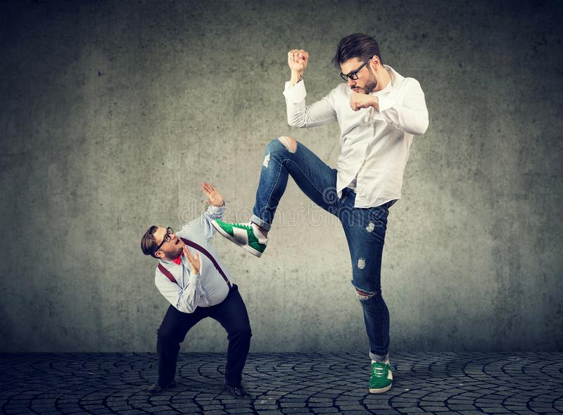 Little businessman being crushed by a giant hipster guy royalty free stock images