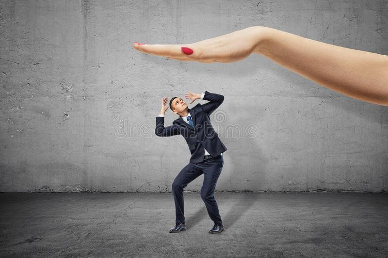 Little businessman covering head with hands and looking up at big woman`s hand above ready to swat him. Corporate management. Control over subordinates royalty free stock photo