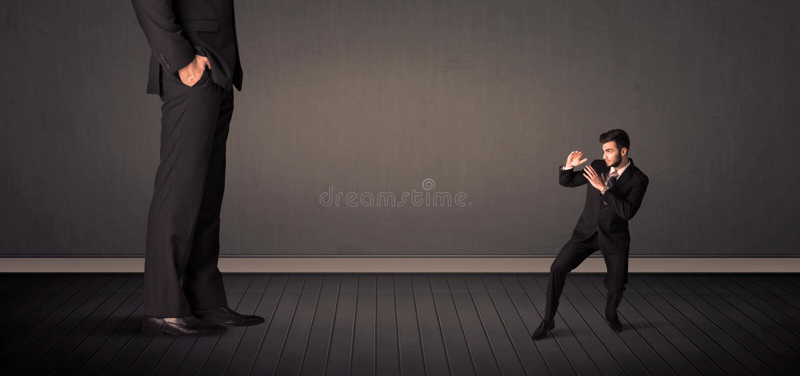 Little bussinesman in front of a giant boss legs concept. On background stock photos