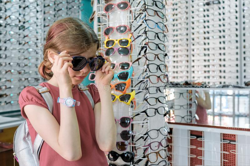Little buyer in the glasses store, girl child chooses sunglasses royalty free stock photos