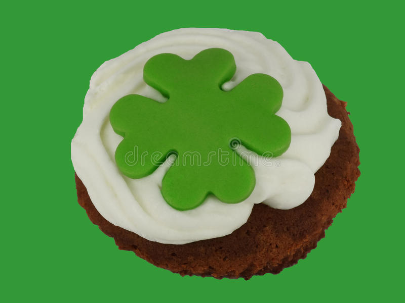 Little cake with cream and green cloverleaf. With green background royalty free stock image
