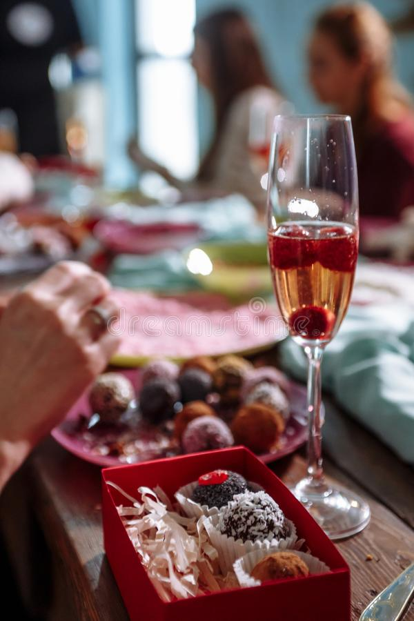 Little cakes in a bowl, a glass of wine with cherries stock photography