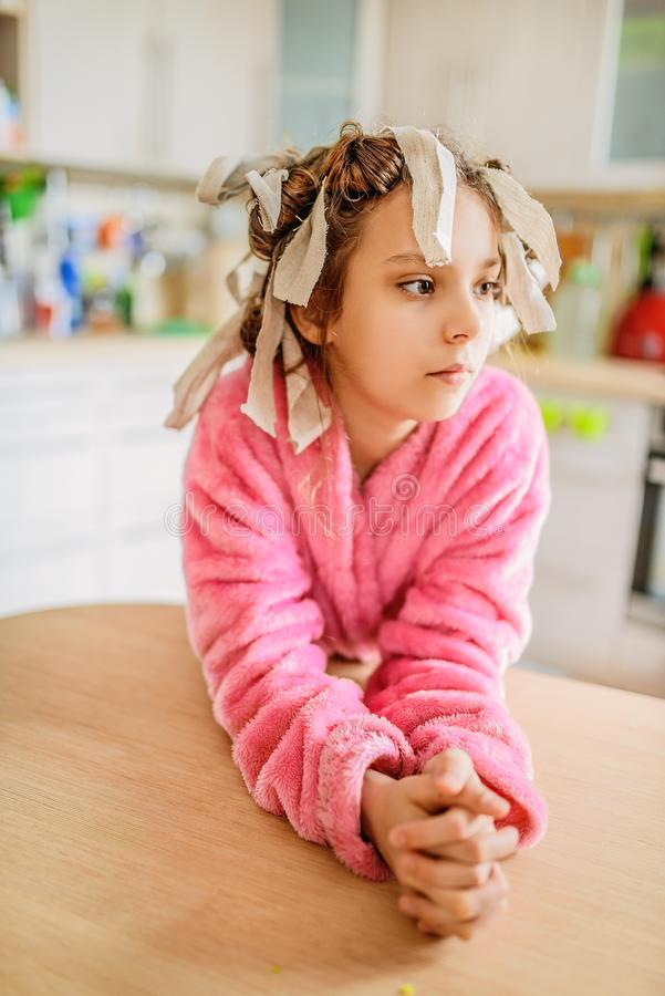 Little calm girl with hair curlers on her head stock photos