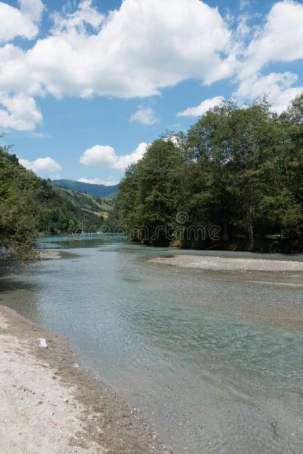 Little calm turquoise river with trees on shore and mountains in the background stock photo