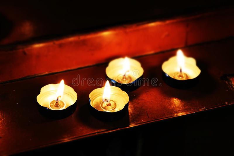 Little candles in a church, miniature style. A detail of some candles on the wooden altar of a church, landscape cut royalty free stock photo