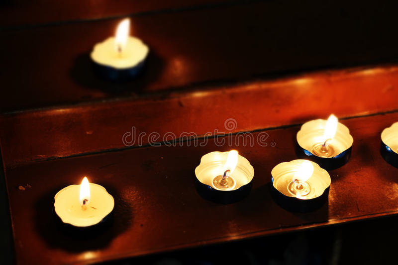 Little candles in a church, miniature style. A detail of some candles on the wooden altar of a church, landscape view stock images
