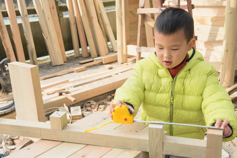 Little carpenter. Chinese kid using measuring tape on carpenters working place site