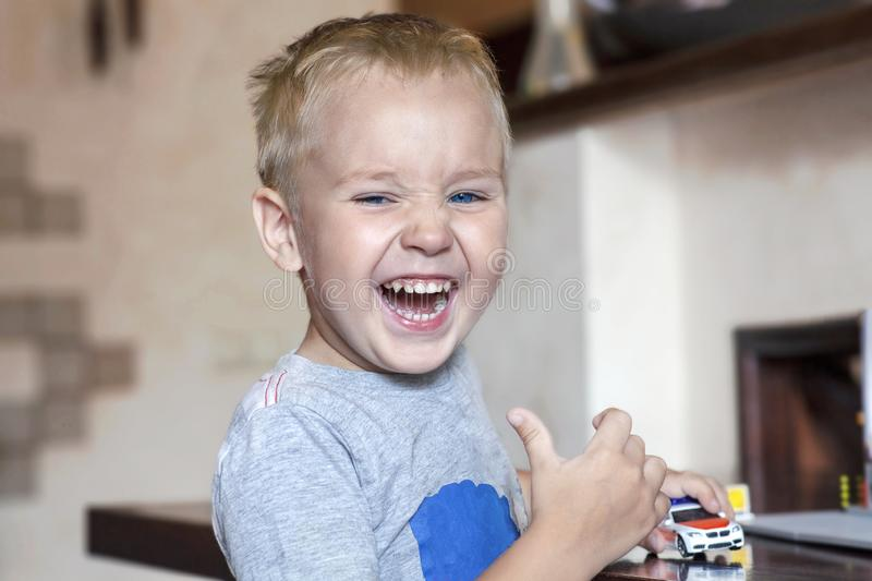 Little caucasian baby boy with blond hair and bright blue eyes laughs holding the car toy and showing thump up. Strong emotions. Indoors, copy space stock photo