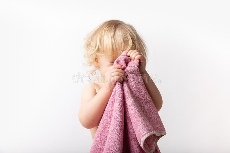 Little Caucasian baby curly girl wipes her face with a pink terry towel over a white background. child hygiene concept stock photos