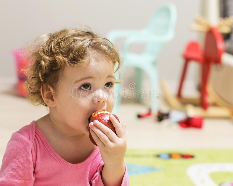 Little Caucasian baby girl in pink bites an apple. A child with curly short hair in the home interior, portrait of a girl royalty free stock photography