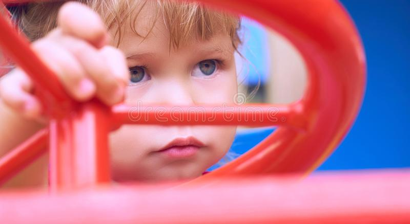 Little Caucasian baby girl sits at the wheel of a toy car. Playing on the playground concept. stock images