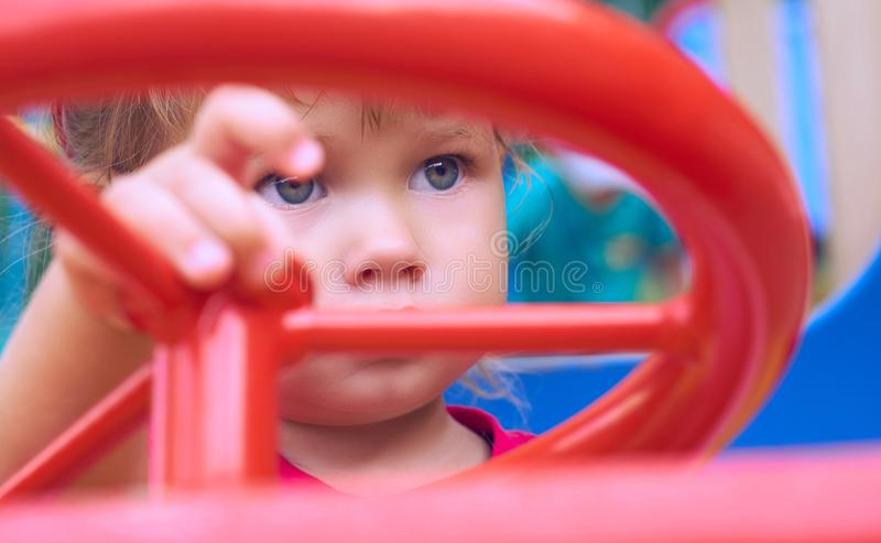 Little Caucasian baby girl sits at the wheel of a toy car. Playing on the playground concept. royalty free stock photo