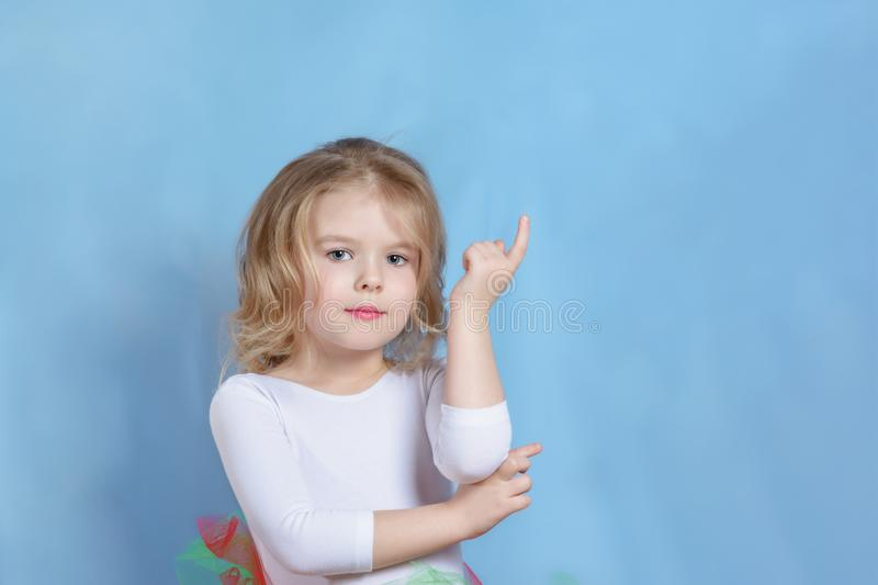 Little Caucasian Blond Girl Model Studio Headshot. Adorable Child with Short Hair Looking at Camera. Pretty Female Kid Reach out Hand with Forefinger Posing on stock photos