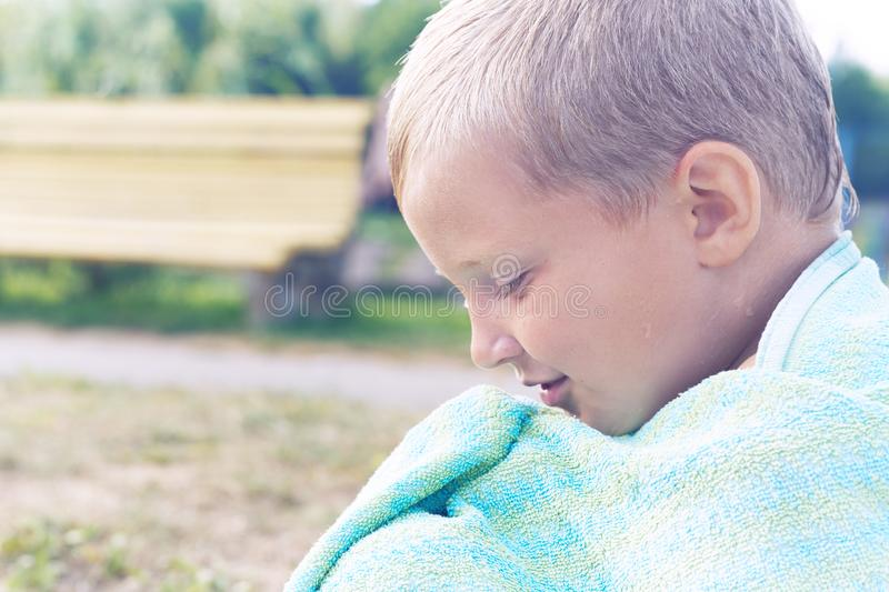 Little Caucasian boy basking after swim in the lake. The boy covered himself with the towel and sits on the shore of the stock image