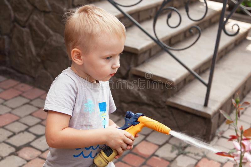 Cute baby boy waters the flowers on the back yard, mother assistant. stock photo