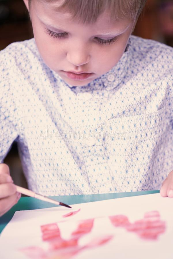 Little blonde Caucasian boy drawing with colorful watercolorsin the kindergarten. School, education concept. stock photography