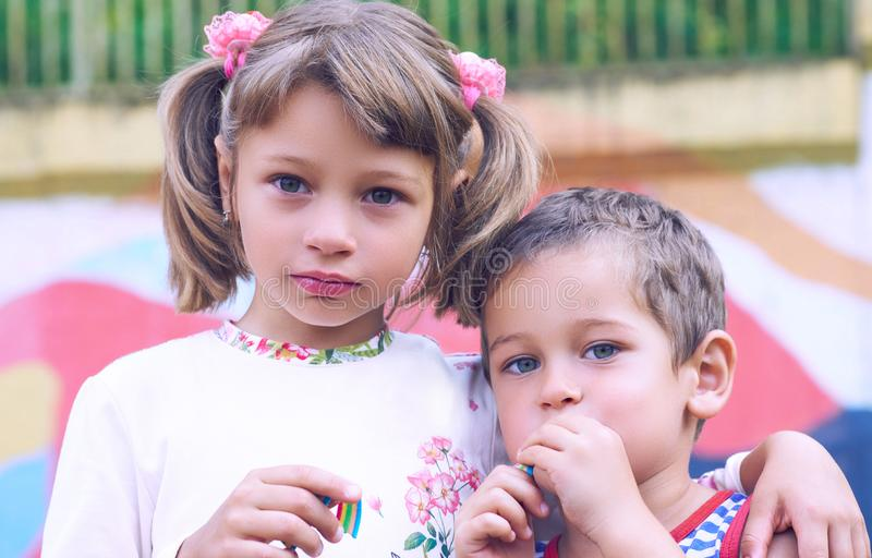 Little Caucasian boy and a girl chewing gum while standing on the playground arm in arm. Image of happy friends having royalty free stock photo