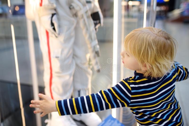 Little caucasian boy looking astronaut space suit in museum. Little blond caucasian boy looking astronaut space suit in museum. Education and entertainment for royalty free stock photo
